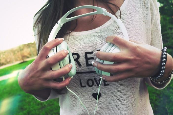 Pige holder et par hvide høretelefoner i naturen